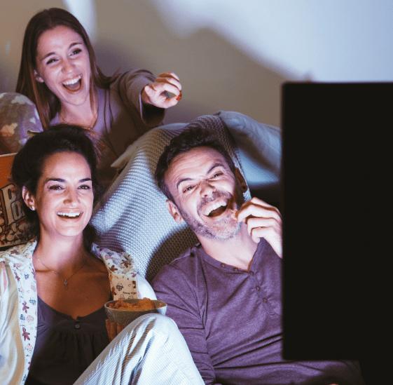Een man en twee vrouwen kijken lachend naar de televisie