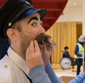 Bezoeker voelt aan de snor van een acteur bij voorstelling van Komt het Zien!